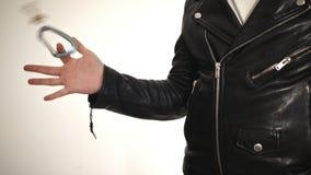 O homem veste um casaco de cabedal preto e gerencie chaves em seus dedos vídeos de arquivo