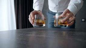 O homem vestido no terno azul formal pôs dois vidros pequenos com álcool sobre a tabela envernizada de madeira vídeos de arquivo