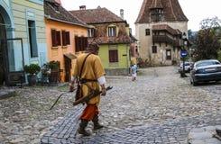 O homem vestido no traje de um arqueiro medieval vai em um de t fotografia de stock