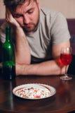 O homem viciado do álcool tem adormecido caído em uma tabela Imagem de Stock