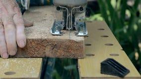 O homem viu uma placa de madeira com uma serra de vaivém elétrica video estoque