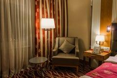 O hotel, cadeira pequena da mesa redonda ao lado de uma lâmpada de assoalho em uma tabela pequena perto da cama é um telefone e u imagem de stock