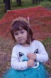 O humor da mola do guarda-chuva do dia do outono da família da criança da menina do elogio, felicidade, árvores de floresta dos o Foto de Stock