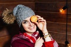 O humor do inverno Morena bonita nova que sorri na roupa e no tampão com as tangerinas no fundo de madeira Fotografia de Stock Royalty Free