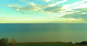 O hyperlapse a?reo do por do sol e as nuvens acima do zang?o de Timelapse da costa de mar voam perto do banco do oceano Horizonta video estoque