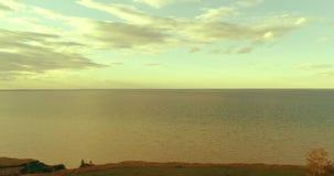 O hyperlapse a?reo do por do sol e as nuvens acima do zang?o de Timelapse da costa de mar voam perto do banco do oceano Horizonta filme