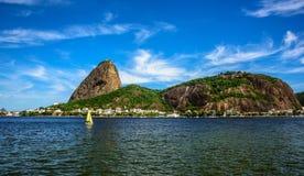 O iate da navigação, a montanha de Sugarloaf e Botafogo pequenos amarelos latem, Rio de janeiro Fotografia de Stock Royalty Free