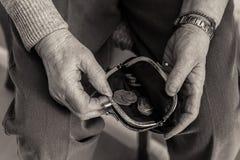 O ` idoso s da senhora entrega a verificação do dinheiro em sua bolsa fotografia de stock royalty free