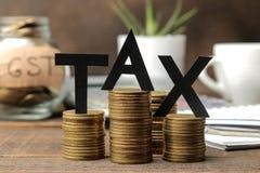 O imposto da palavra e uma pilha de moedas com uma pena e um café do caderno em um fundo de madeira marrom imagem de stock royalty free