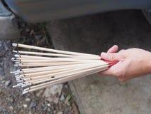 O incenso ardente cola guardar sobre uma mão com fumo de ondulação Fotos de Stock