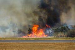 O incêndio de escova do aeroporto na pista de decolagem fecha o aeroporto Imagens de Stock