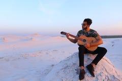 O indivíduo árabe atrativo canta músicas na guitarra, sentando-se no monte dentro imagens de stock