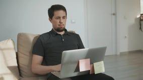 O indivíduo adulto trabalha como um freelancer em um portátil em seu apartamento onde lá o ` s um gato vídeos de arquivo