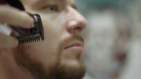O indivíduo africano considerável faz o corte de cabelo novo no salão de beleza da barbearia Processo masculino do tratamento da  video estoque