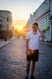 O indivíduo ajusta seus vidros no por do sol Foto de Stock Royalty Free