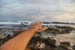 O indivíduo alcança para fora às nuvens O indivíduo puxa sua mão para o mar fotografia de stock