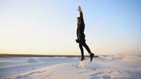 O indivíduo alegre do xeique dos UAE do Arabian comunica-se no telefone e salta-se na linha do movimento lento no meio do deserto filme