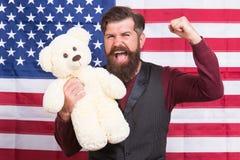O indivíduo americano com brinquedo comemora o feriado Feriado americano Fundo farpado da bandeira americana de urso de peluche d fotos de stock