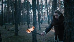 O indivíduo atravessa a floresta com uma tocha vídeos de arquivo