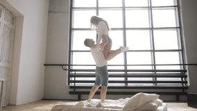 O indivíduo aumenta sua amiga em seus braços sobre ele na cama Pares novos que flertam video estoque
