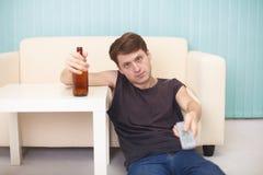 O indivíduo bêbedo com o frasco da cerveja, tevê muda as canaletas imagens de stock royalty free