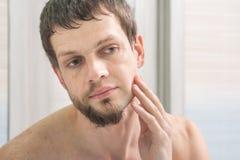 O indivíduo barbeou um meio de seus cara e olhares no espelho que avalia o resultado imagem de stock royalty free