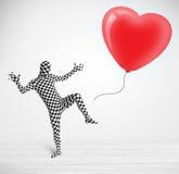 O indivíduo bonito no terno do corpo do morpsuit que olha um balão deu forma ao coração Imagem de Stock Royalty Free