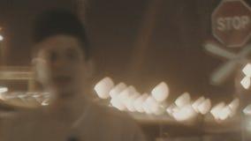 O indivíduo branco novo que bate na rua na noite perto da ponte vídeos de arquivo