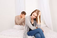 O indivíduo com a menina senta a virada na cama fotos de stock royalty free