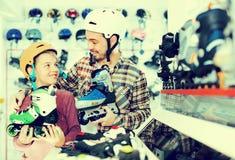 O indivíduo com seu paizinho que ajuda-se escolhe calçados Foto de Stock