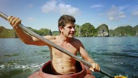O indivíduo com torso desencapado enfileira o caiaque lentamente contra a baía e as ilhas video estoque