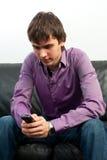 O indivíduo com um telefone móvel foto de stock