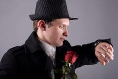O indivíduo com uma rosa olha o relógio Fotografia de Stock