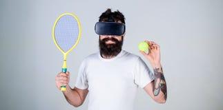 O indivíduo com vidros de VR joga o tênis com raquete e bola O homem com a barba em vidros de VR joga o tênis, fundo cinzento hip Fotos de Stock