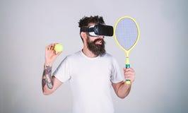 O indivíduo com vidros de VR joga o tênis com raquete e bola O homem com a barba em vidros de VR joga o tênis, fundo cinzento vir fotografia de stock
