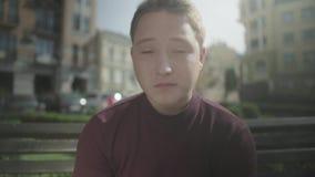 O indivíduo come com prazer ao sentar-se em um banco vídeos de arquivo