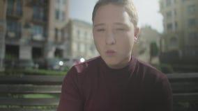 O indivíduo come microplaquetas com prazer ao sentar-se em um banco video estoque
