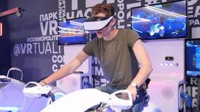 O indivíduo considerável atrativo novo monta uma motocicleta na realidade virtual Feriados, inovação, tela, néon, bicicleta, fres filme