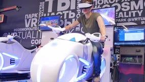 O indivíduo considerável atrativo novo monta uma motocicleta na realidade virtual Feriados, inovação, tela, néon, bicicleta, fres video estoque