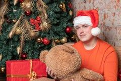O indivíduo considerável do indivíduo no chapéu de Papai Noel abraça o urso que senta-se sob a árvore cercada por caixas dos pres imagem de stock royalty free