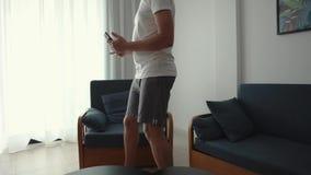 O indivíduo considerável está andando na sala de visitas pequena, sentando-se na cadeira com móbil filme