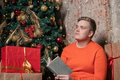 O indivíduo considerável está lendo um livro que senta-se sob a árvore cercada por caixas dos presentes Natal e presentes fotografia de stock