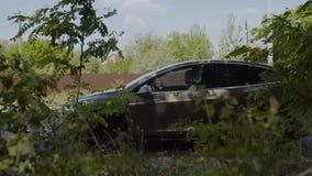 O indivíduo considerável novo veio pelo carro e sai de seu automóvel filme