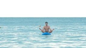 O indivíduo considerável senta-se na pose Lotus na placa de pá no oceano filme