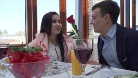 O indivíduo dá à menina uma rosa vermelha no restaurante na tabela e beijam o vídeo conservado em estoque da metragem vídeos de arquivo
