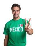 O indivíduo de riso em um jérsei mexicano que mostra a vitória assina fotos de stock