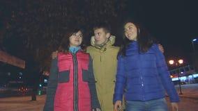 O indivíduo e duas meninas atravessam a aleia Abraça-os filme