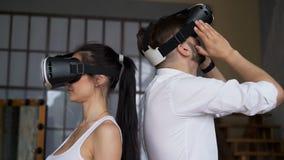 O indivíduo e a menina em vidros modernos de VR olham ao redor vídeos de arquivo