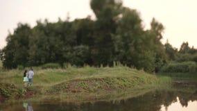 O indivíduo e a menina estão andando ao longo da lagoa vídeos de arquivo