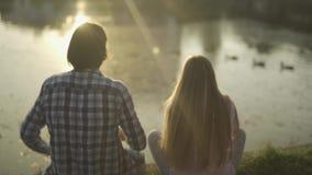 O indivíduo e a menina estão sentando-se no banco de rio vídeos de arquivo